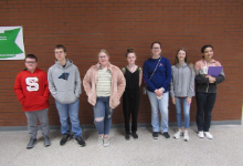 students standing in front of brick wall