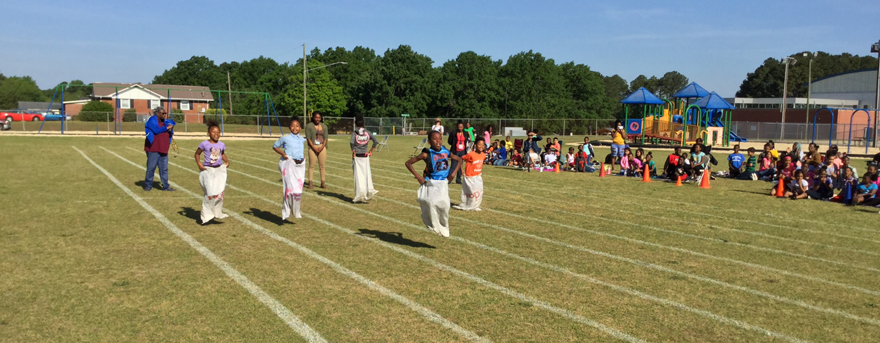 Carver Height Elementary students having a sack race outside.