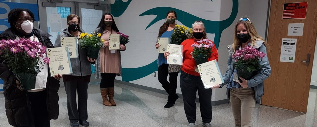 Staff members of the year holding flowers and certificates